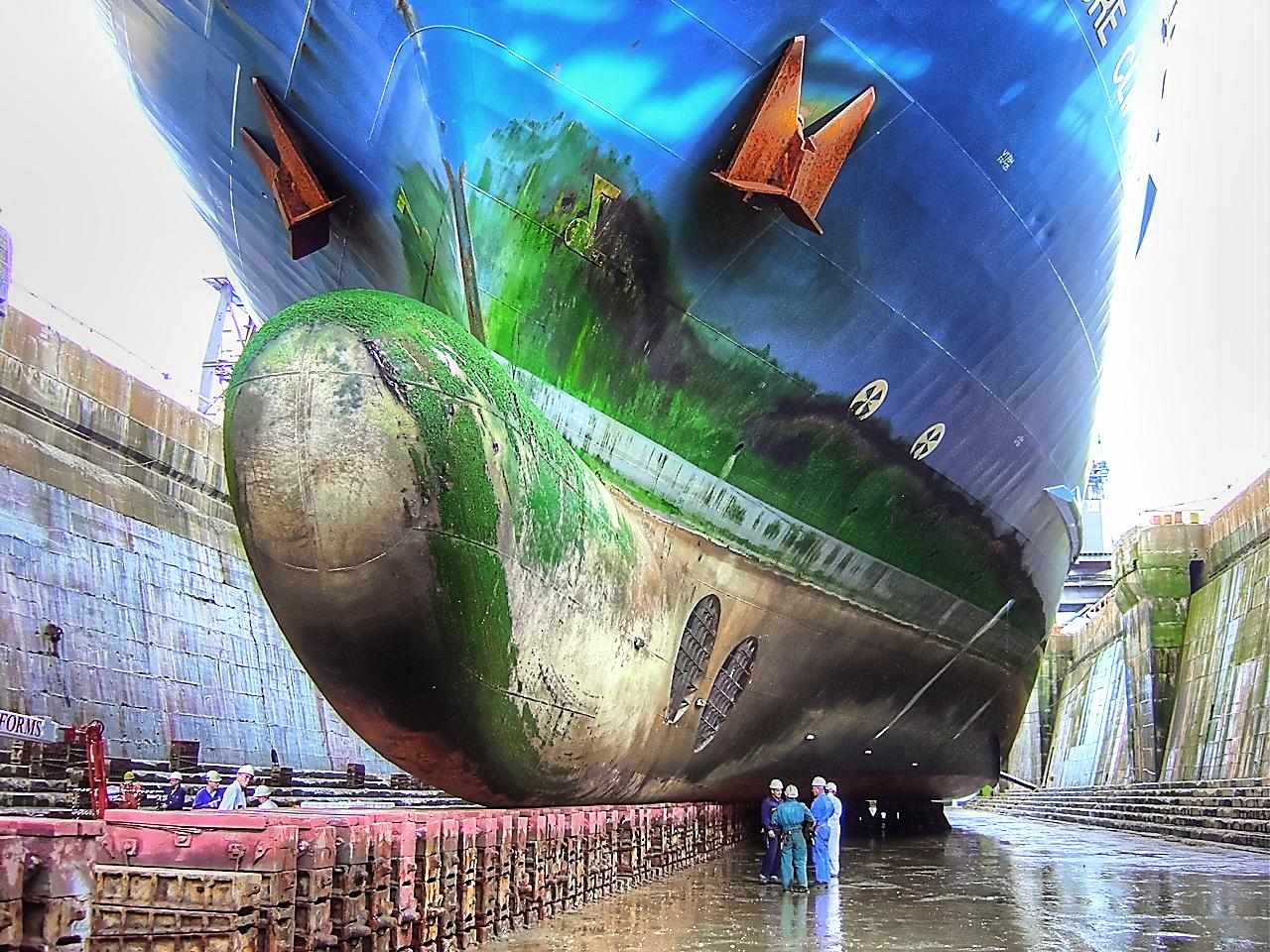 ship in drydock with mechanics discussing the green slime on the hull